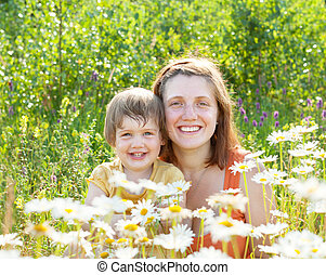 happy woman with baby in daisy plant