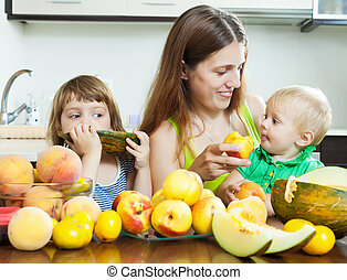 happy woman with children eating fruits
