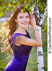 Portrait of happy woman with curled hair outdoors near birch in sunset sun