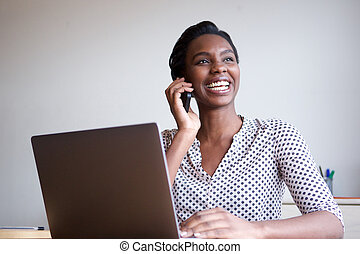 happy woman with laptop talking on mobile phone