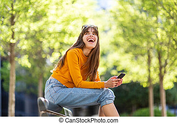 happy woman with mobile phone in park