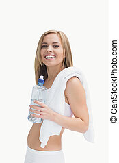 Portrait of happy woman with towel holding water bottle