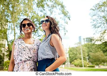 portrait of happy women or friends at summer park