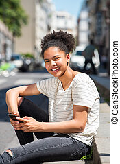 happy young african american girl sitting outside in city holding mobile phone