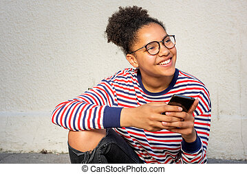 happy young african american girl sitting with cellphone