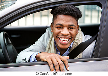 happy young african american man smiling while in car