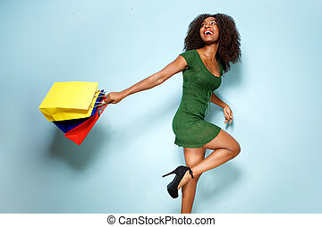 happy young african american woman holding shopping bags on blue background