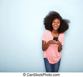 happy young african american woman holding smart phone