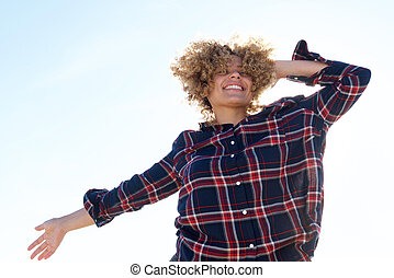 happy young african american woman laughing with hand in hair outside