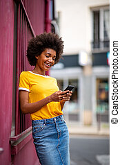 happy young african american woman looking at cellphone outside in city