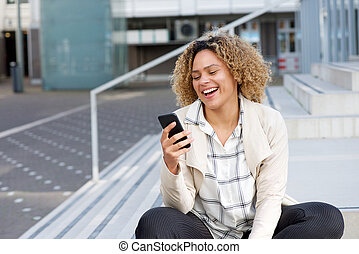 happy young african american woman looking at mobile phone outside