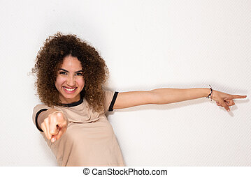 happy young african american woman pointing fingers by white background