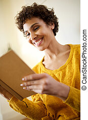 happy young african american woman reading book