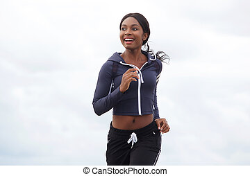 happy young african american woman running outdoors