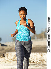happy young african american woman running outside
