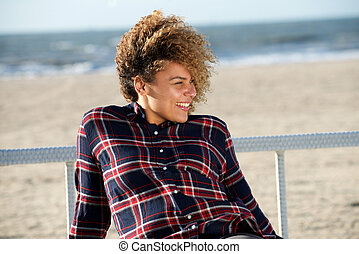 happy young african american woman sitting at beach