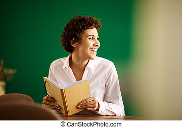 happy young african american woman sitting at table with book