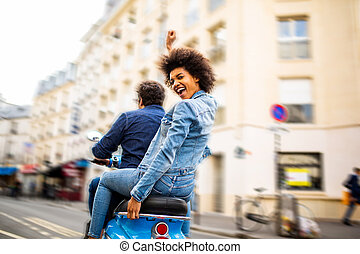 happy young african american woman sitting on back of scooter driving through city streets with arms raised