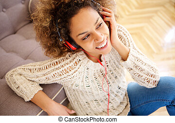 happy young african american woman sitting on floor and listening to music with headphones