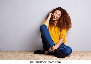 happy young african american woman sitting on floor by gray wall