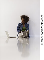 african american woman sitting on floor with laptop