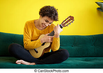happy young african american woman sitting on sofa with guitar instrument