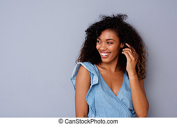 Portrait of happy young african american woman smiling against gray background