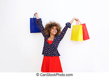 happy young african american woman smiling holding shopping bags