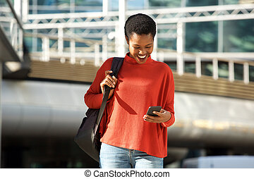 happy young african american woman smiling with cellphone in city