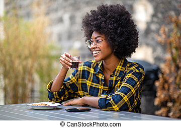 happy young african american woman smiling with cup of coffee