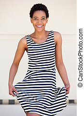 happy young african american woman striped dress