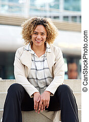 happy young african american woman with curly hair sitting on steps in city