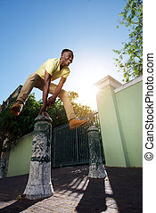 happy young african man jumping over iron post on sidewalk
