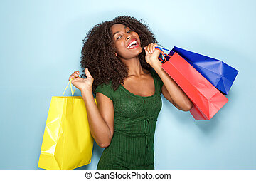 happy young african woman holding many shopping bags on blue background