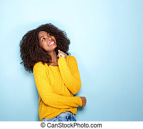 happy young african woman looking up on blue background