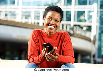 happy young african woman smiling with mobile phone in city