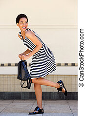 happy young african woman striped dress holding bag
