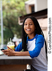 happy young african woman with mobile phone at outdoor cafe