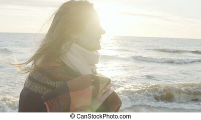 Portrait of happy young attractive woman smiling in camera on the shore of the sea. Female raises hands up with plaid.