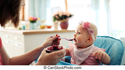 Portrait Of Happy Young Baby In High Chair being fed
