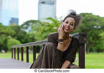 Portrait of happy young beautiful African woman talking on the phone at the park