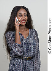 Portrait of happy young beautiful African woman talking on the phone