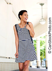 happy young black woman in striped dress walking outdoors