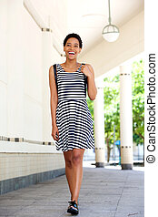 happy young black woman in striped dress walking outside