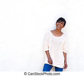 Portrait of happy young black woman laughing against white background