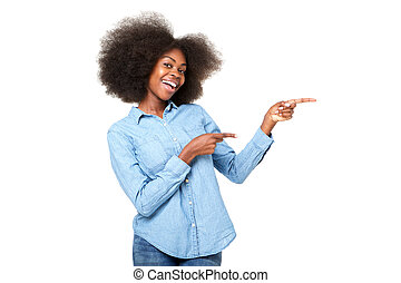 happy young black woman with afro pointing fingers at copy space