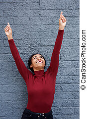 happy young black woman with arms raised and fingers pointing up