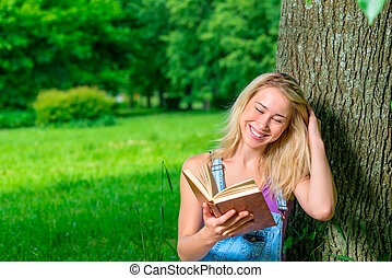 portrait of happy young blonde with a book