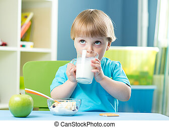Portrait of happy young boy holding glass with milk