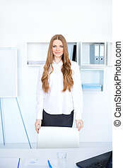 Portrait of happy young business woman standing in bright office